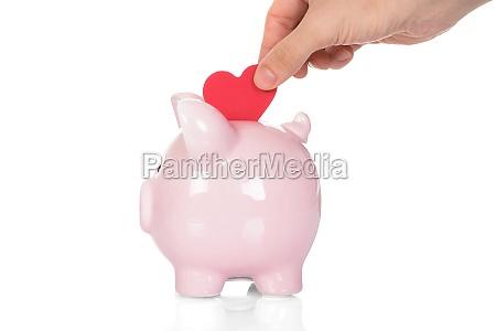 hand deposit red heart in piggy