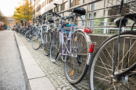 bicycles parked against a railing
