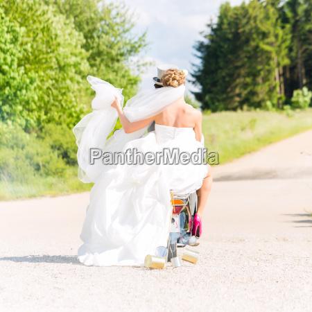 hochzeitspaar faehrt motorroller in hochzeitskleid und