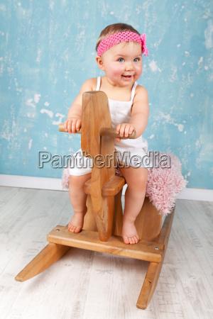 kleinkind auf schaukelpferd