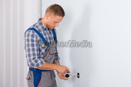 electrician installing electrical socket