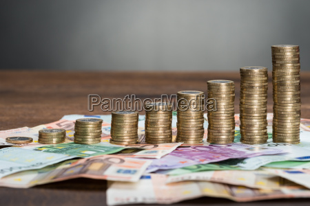 stacked coins arranged on banknotes