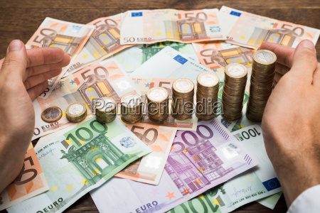 businessman protecting coins and banknotes