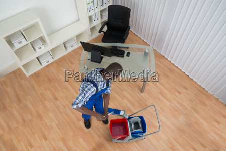 janitor cleaning floor with mop in
