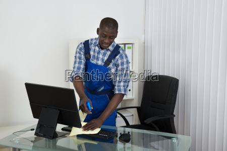janitor cleaning glass desk with cloth