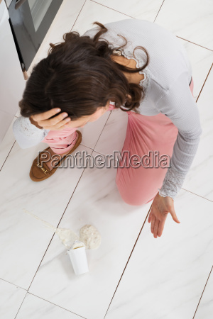 woman looking at yoghurt spilled on