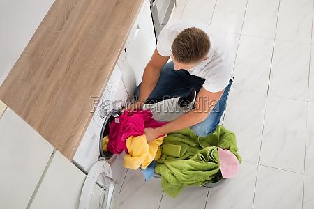 man putting clothes in washing machine