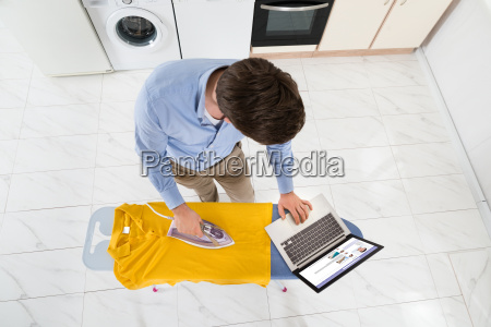 man with laptop while ironing t