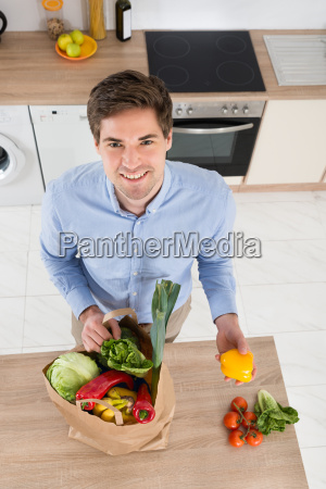 man removing vegetables from grocery bag