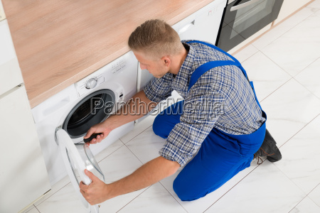 worker in overall fixing washer