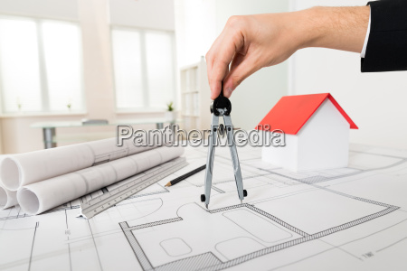 architect hands holding compass on blueprint