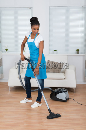 woman cleaning floor with vacuum cleaner