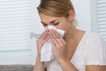 woman blowing nose while suffering from