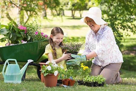 happy grandmother with her granddaughter gardening