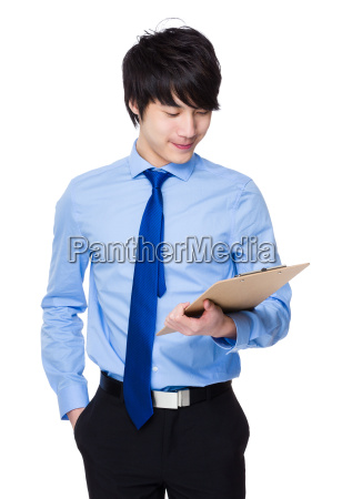 asian young businessman write on clipboard