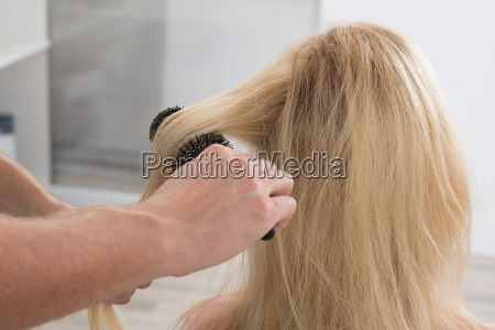 hairstylist brushing womans hair