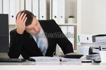 tensed accountant sitting at desk in