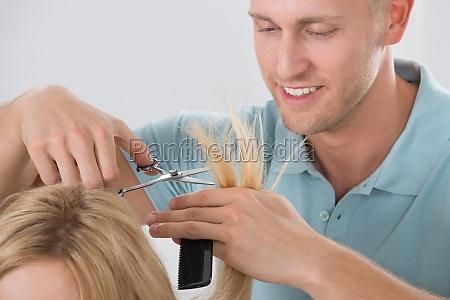 hairdresser cutting customers hair at salon