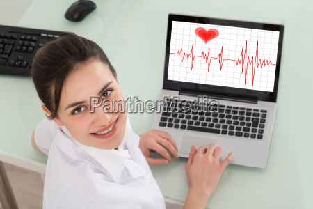 female doctor with laptop showing heartbeat