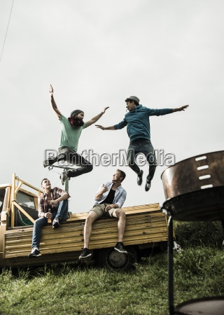 two friends jumping from pick up