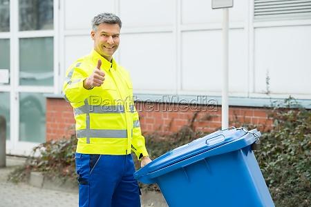 working man holding dustbin on street