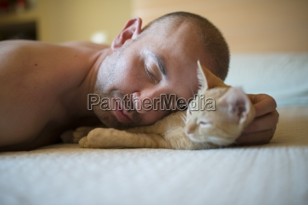 man and kitten lying on bed
