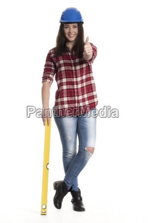 weiblicher handwerker mit wasserwaage zeigt daumen