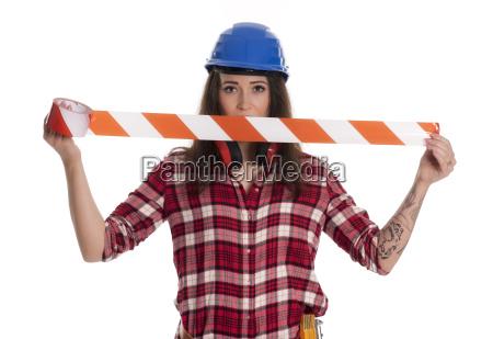 weiblicher handwerker haelt flatterband hoch