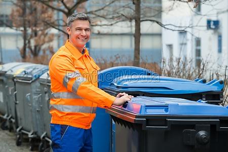 working man standing near dustbin on