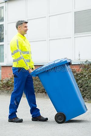 male worker walking with dustbin on