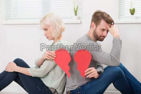 sad couple holding red broken heart