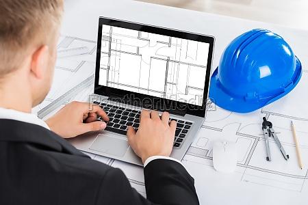 architect analyzing blue print on computer