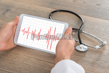 male doctor showing heartbeat on digital