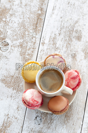 cup of coffee with five macarons