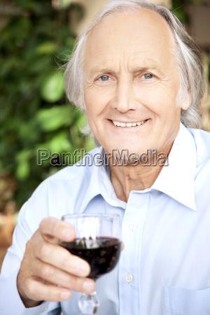 portrait of relaxed senior man holding