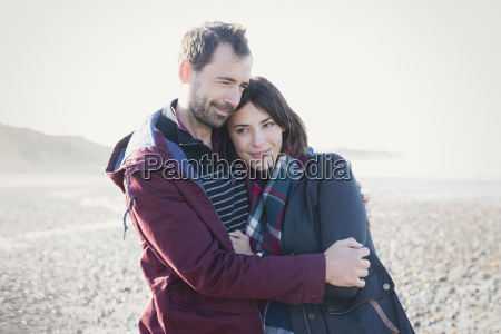 couple hugging on sunny beach