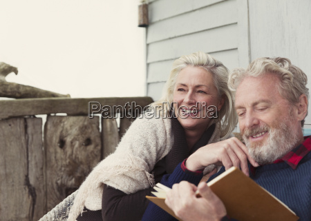 smiling senior couple reading book on
