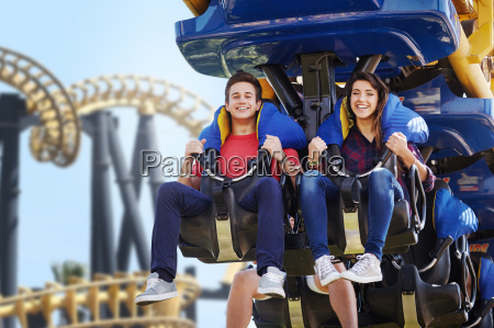 young couple riding amusement park ride
