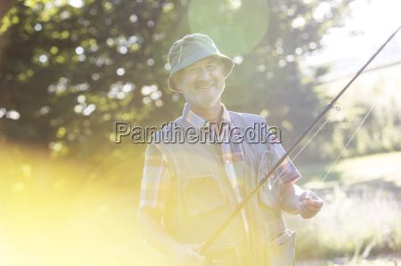portrait smiling senior man with fishing