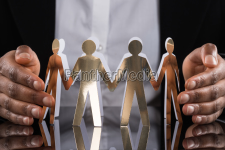 businessperson protecting cut out figures