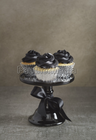 three cup cakes with black buttercream