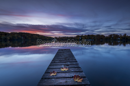 wooden boardwalk on lake with autum