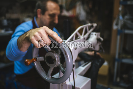 shoemaker using a sewing machine in