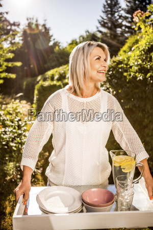 mature woman carrying tray with dish