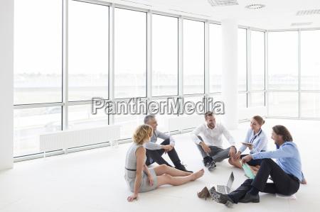 businesspeople sitting on the floor talking
