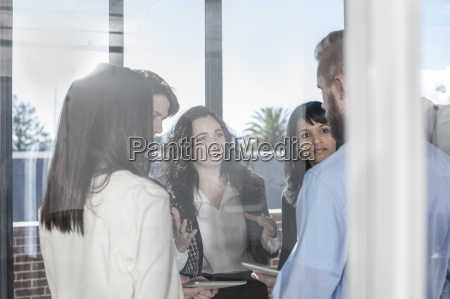 businesspeople talking at the window