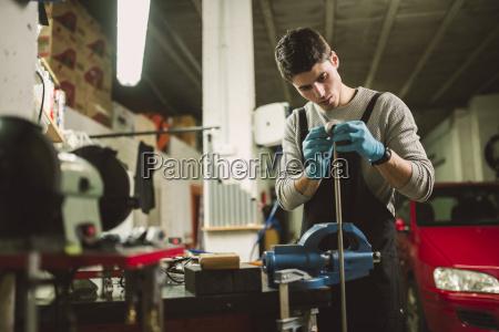 young mechanic working in repair garage