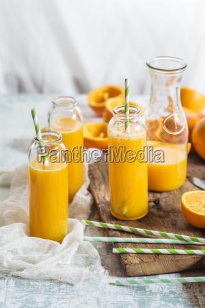 sliced oranges and glass bottles of