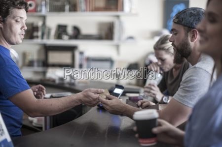 young man paying with credit card