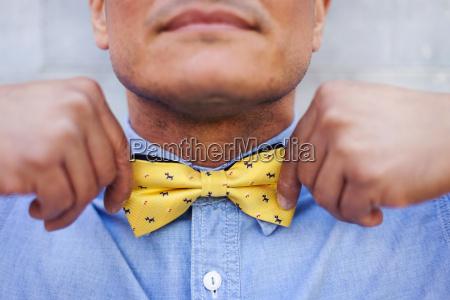 mature man tying bow tie close